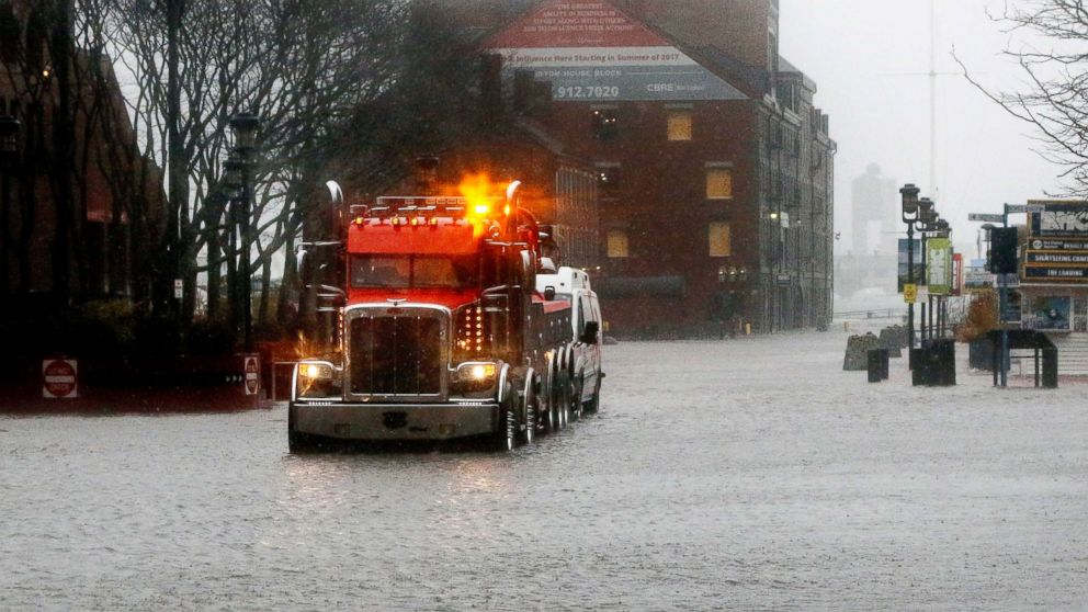 A wrecker tows a vehicle stranded on State Street by water from Boston Harbor at high tide, March 2, 2018, in Boston.