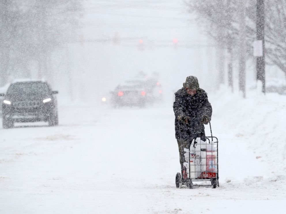 PHOTO: A man walks with his groceries in a cart during a heavy snowfall, Dec. 29, 2017, in Erie, Pa.