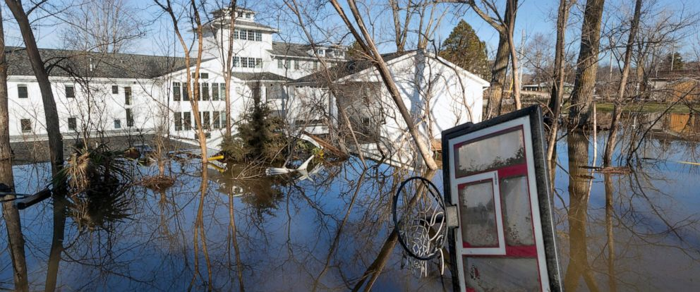 PHOTO: A wayward basketball hoop is seen behind a flooded home Friday, March 22, 2019, in Bellevue, Nebraska.