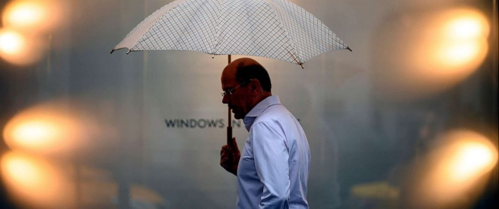 PHOTO: A man holding an umbrella passes a window of a shop in midtown Manhattan on July 30, 2019, in New York City.