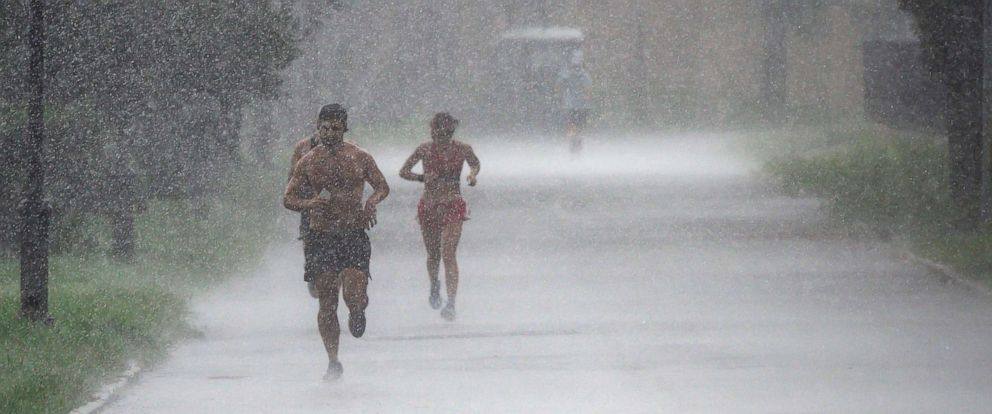 PHOTO: Joggers run in a park during a downpour on Aug. 9, 2019, in New York City.