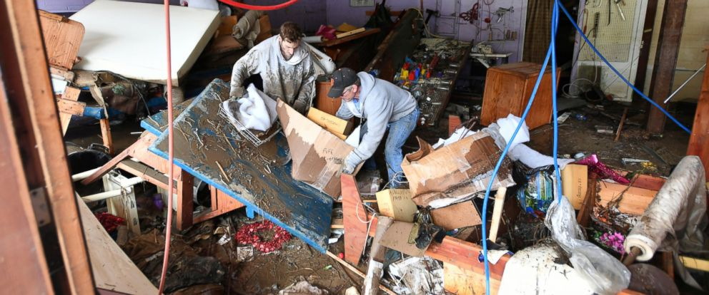 PHOTO: Mick Meguinn, right, and his son Michael Meguinn help clean up Micks girlfriends store as flood waters continue to recede in Guerneville, California, on Friday, March, 1, 2019.
