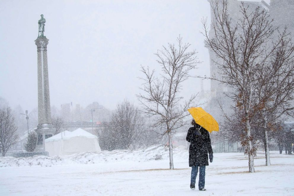 PHOTO: Sarah Wilson walks down the hill along Kellogg Avenue in St. Paul,. Minn., with an umbrella to shield the wind and snow, Jan. 22, 2018.