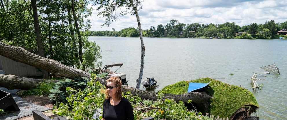 PHOTO: Patti Ray surveys the damage to her lakeside property, July 29, 2019, in Scandia, Minn.