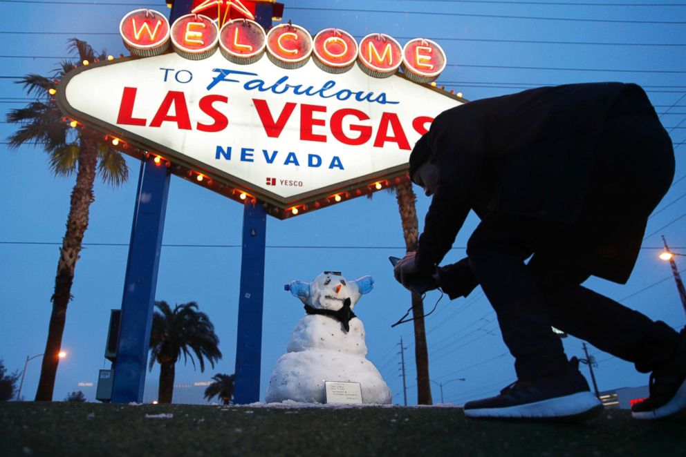 """A man, who declined to give his name, takes a picture of a small snowman at the """"Welcome to Fabulous Las Vegas"""" sign along the Las Vegas Strip, Feb. 21, 2019, in Las Vegas."""