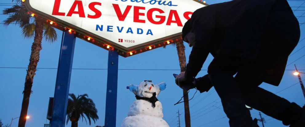 """PHOTO: A man, who declined to give his name, takes a picture of a small snowman at the """"Welcome to Fabulous Las Vegas"""" sign along the Las Vegas Strip, Feb. 21, 2019, in Las Vegas."""