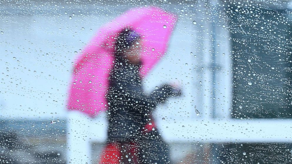 Raindrops are seen on a vehicle's window as a woman walks by using an umbrella under heavy rainfall in Los Angeles, March 21, 2018.