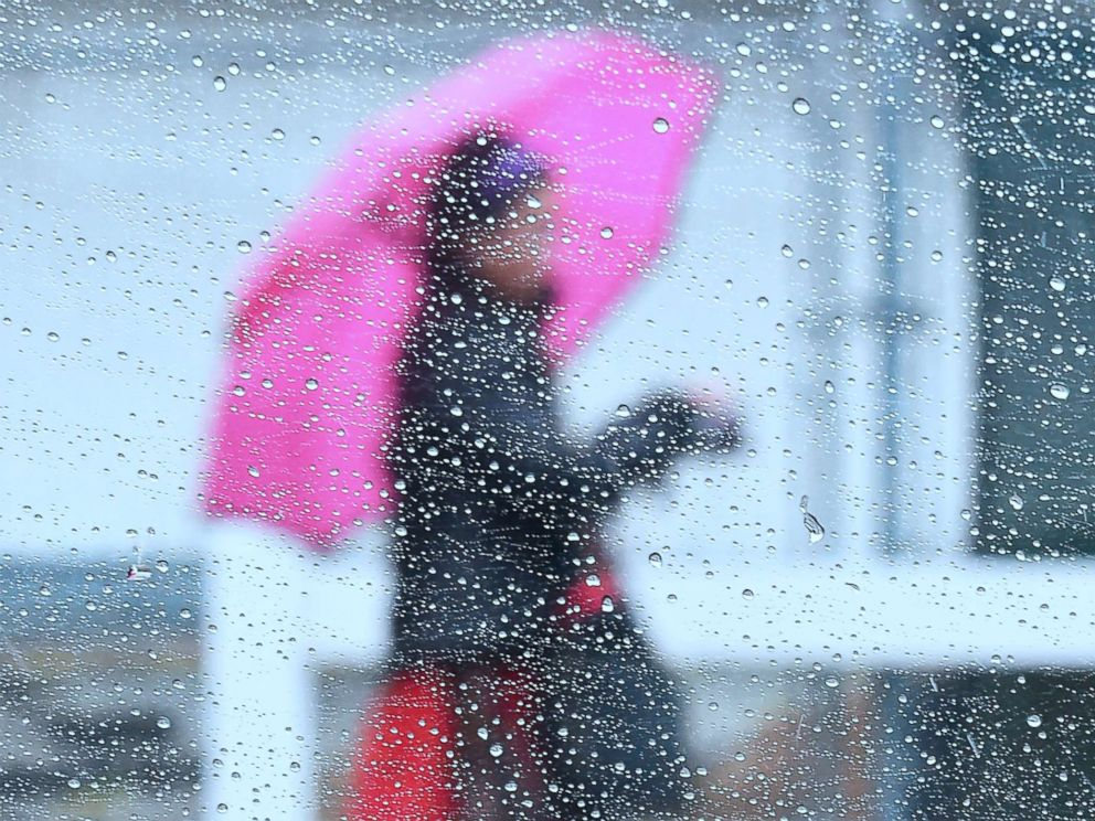 PHOTO: Raindrops are seen on a vehicles window as a woman walks by using an umbrella under heavy rainfall in Los Angeles, March 21, 2018.