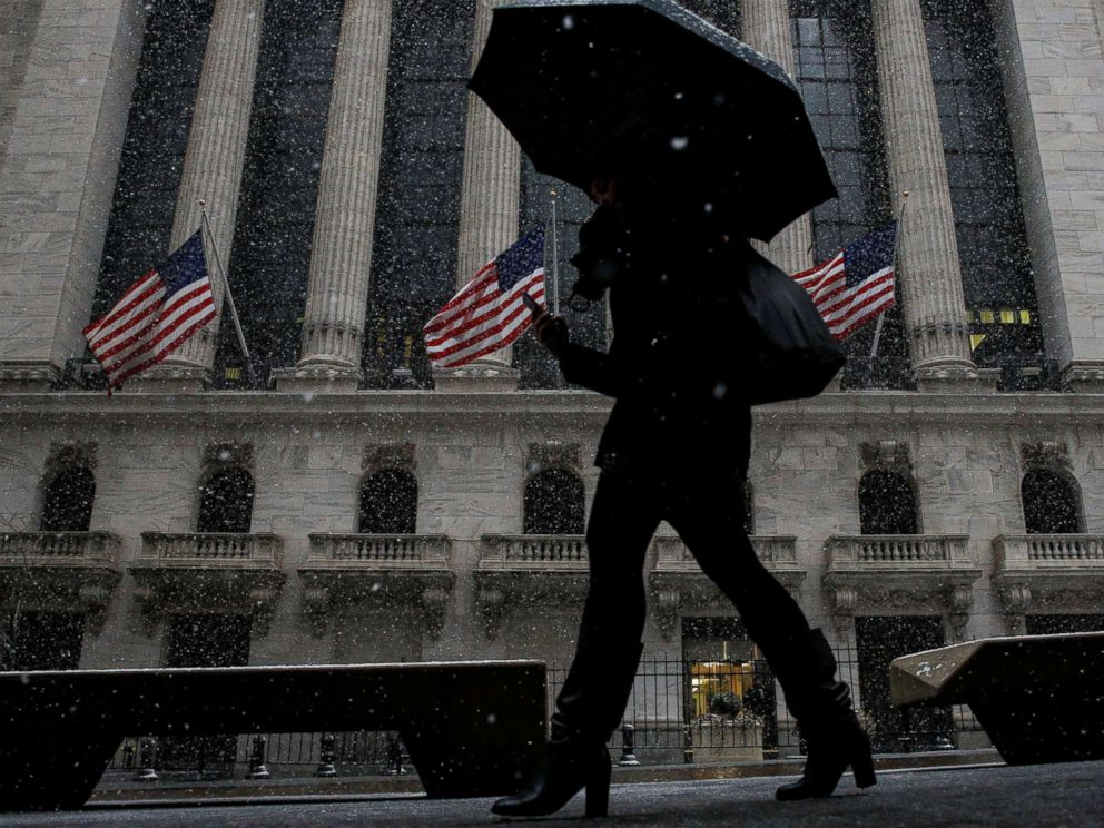 PHOTO: Snow begins to fall as morning commuters pass by the New York Stock Exchange, in New York, Feb. 7, 2018.