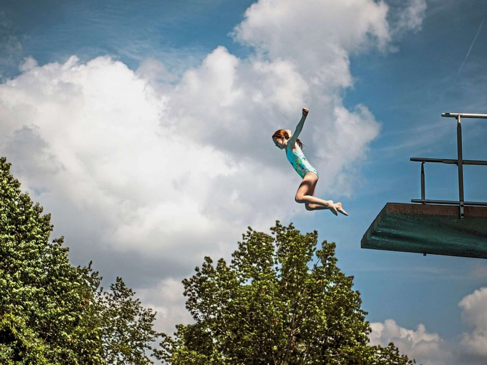 PHOTO: Abby Swank, 10, of Robinson, leaps off a diving board at the pool at Settlers Cabin Park, Thursday, July 18, 2019, in Robinson, Pa.