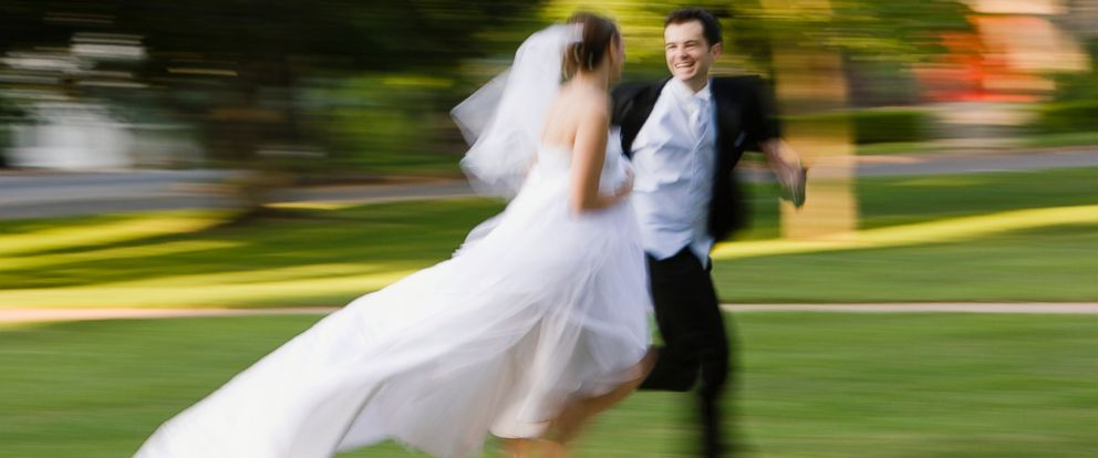 PHOTO: Bride and groom is running side by side in this stock image.