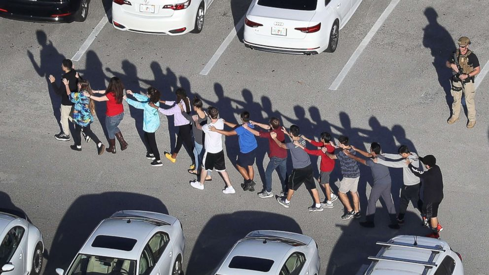 People are brought out of the Marjory Stoneman Douglas High School after a shooting at the school that reportedly killed and injured multiple people on Feb. 14, 2018, in Parkland, Fla.