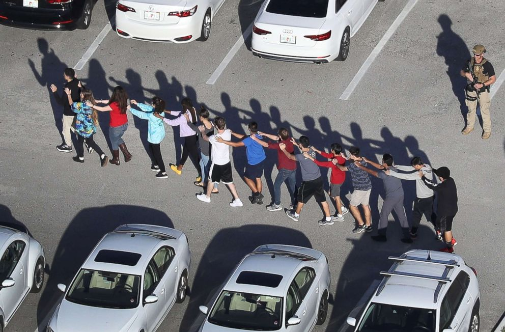 PHOTO: People are brought out of the Marjory Stoneman Douglas High School after a shooting at the school that reportedly killed and injured multiple people on Feb. 14, 2018, in Parkland, Fla.