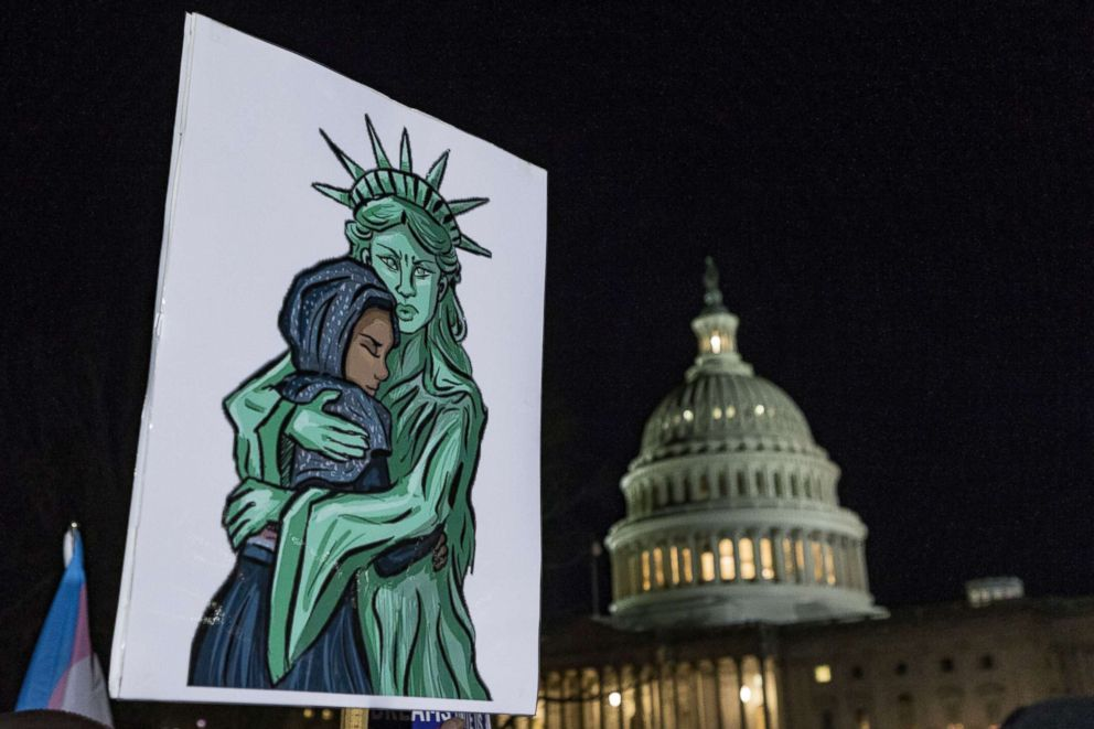 A sign depicts the Statue of Liberty embracing an immigrant during a protest against the termination of the Deferred Action for Childhood Arrivals program (DACA) at the Capitol on the eve of a government shutdown, Jan. 19, 2018, in Washington, D.C.