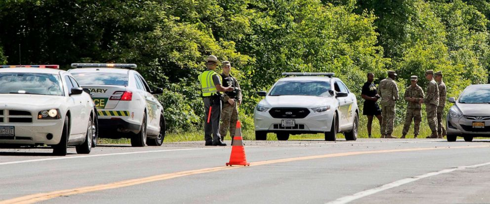 PHOTO: Military police and civilian first responders stand along Route 293 in response to a rollover of a truck in which at least one person was killed on Thursday, June 6, 2019, in Cornwall, N.Y.