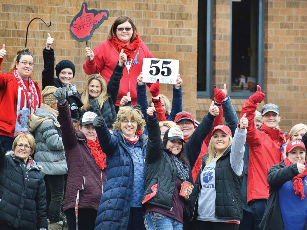 PHOTO: Teachers give a thumbs-up in front of Woodsdale Elementary in Wheeling, W. Va., on March 6, 2018, after teachers across the state received notice that a deal was reached to end the teacher walkout.