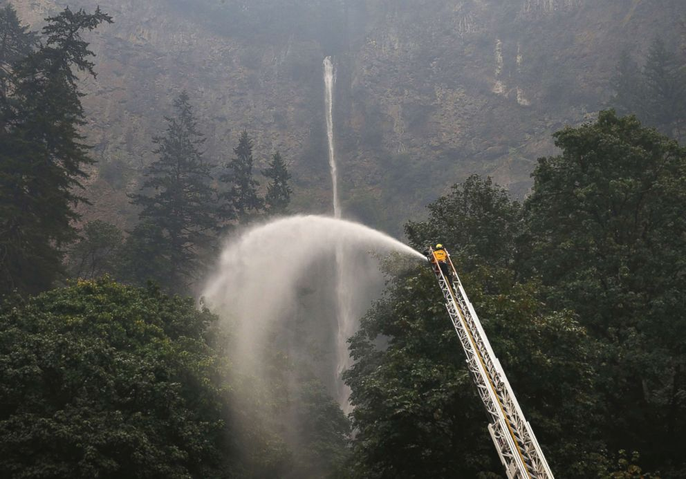 PHOTO: A firefighter sprays water on the trees around Multnomah Falls, Sept. 6, 2017, as the Eagle Creek Fire continues to burn east of Troutdale, Ore.