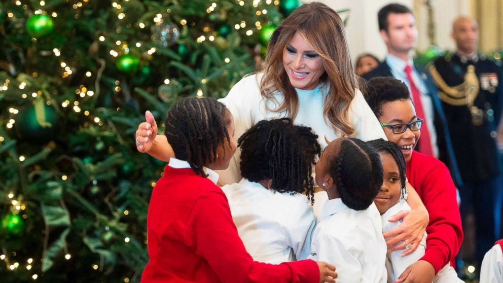 First Lady Melania Trump hugs children in the East Room as she tours Christmas decorations at the White House, Nov. 27, 2017.