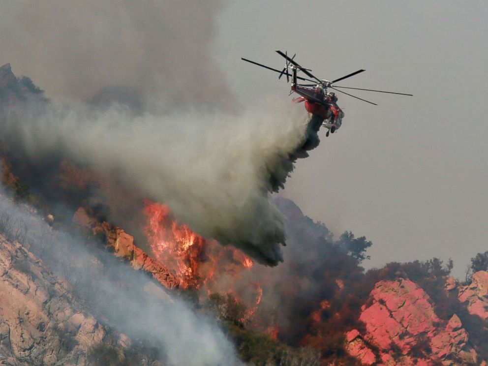 PHOTO: A helicopter drops flame retardant on a wildfire, Nov. 10, 2018, in Malibu, Calif. The Woolsey fire has burned over 70,000 acres and has reached the Pacific Coast as it continues grow.