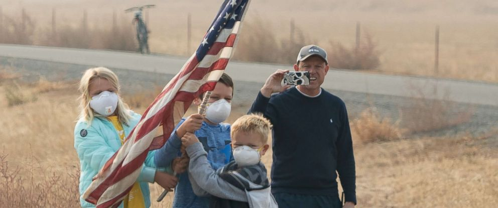 PHOTO: People wearing masks to watch the motorcade of President Donald Trump as he drives to view damage from wildfires in Paradise, Calif., Nov. 17, 2018.