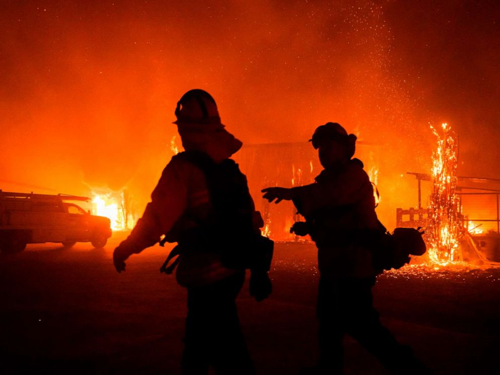 PHOTO: Firefighters give direction as a wind-driven fire burns a structure on a farm during the Kincade fire in Windsor, Calif., Oct. 27, 2019.
