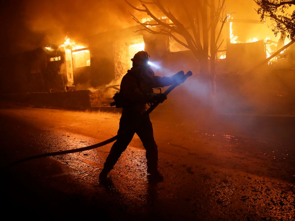 PHOTO: A firefighter gets in position to hose down flames as a home burns in the Getty fire area, Oct. 28, 2019, in Los Angeles.