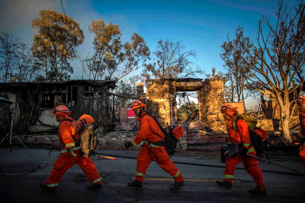 PHOTO: Firefighters walk past a burnt home during the Getty Fire in Brentwood, Calif., Oct. 28, 2019.