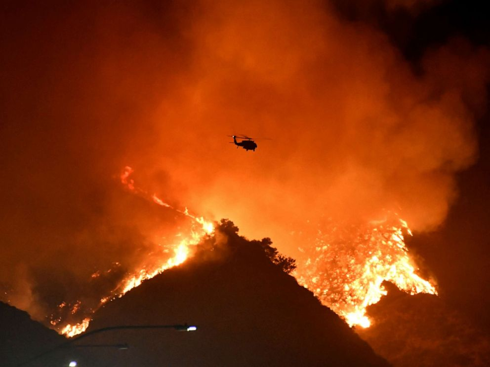 PHOTO: A firefighting helicopter flies over the Getty Fire as it burns in the hills west of the 405 freeway in the hills of West Los Angeles, Oct. 28, 2019.