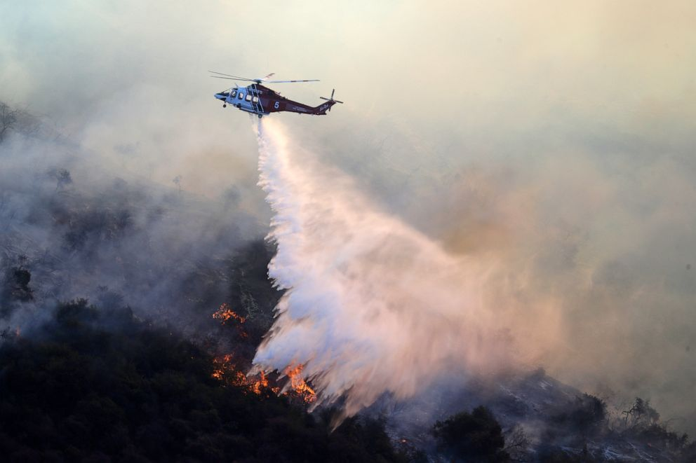 PHOTO: A helicopter drops water as the Getty fire burns on Mandeville Canyon, Oct. 28, 2019, in Los Angeles.