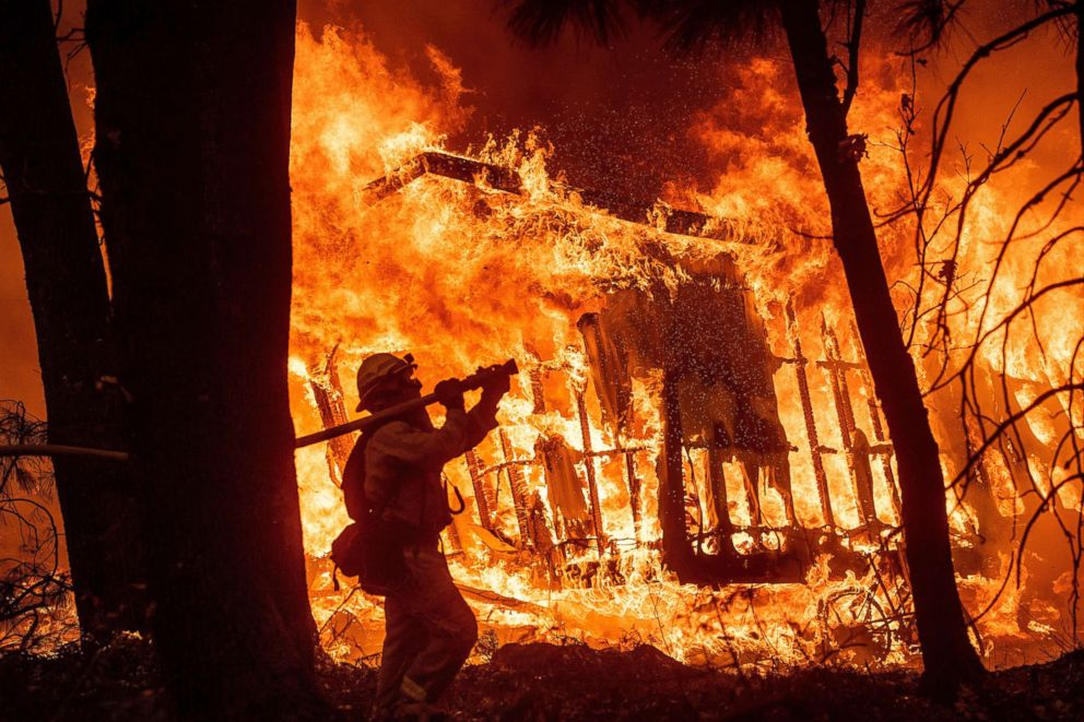 PHOTO: Firefighter Jose Corona sprays water as flames from the Camp Fire consume a home in Magalia, Calif., Nov. 9, 2018.
