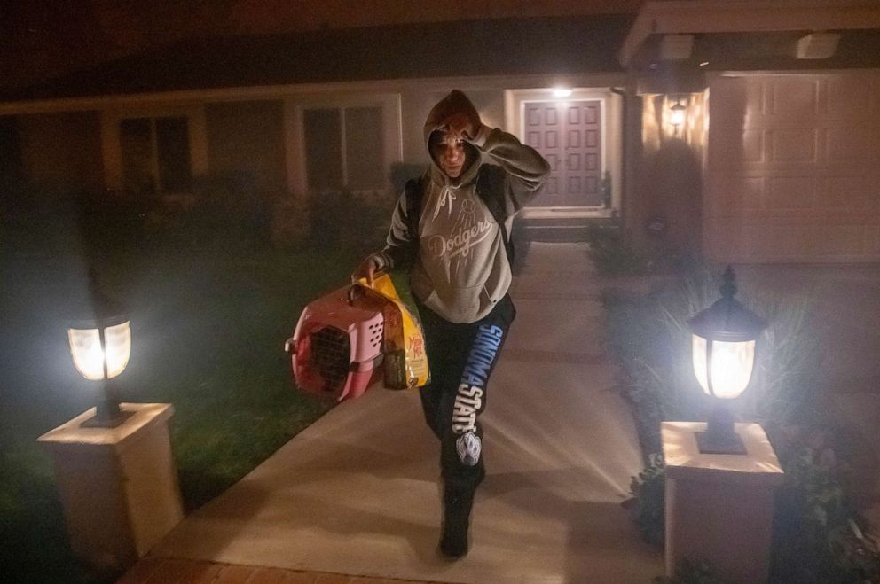 PHOTO: A woman evacuates her home with her cat as the Saddleridge fire threatens homes in Granada Hills, Calif., Oct. 11, 2019.