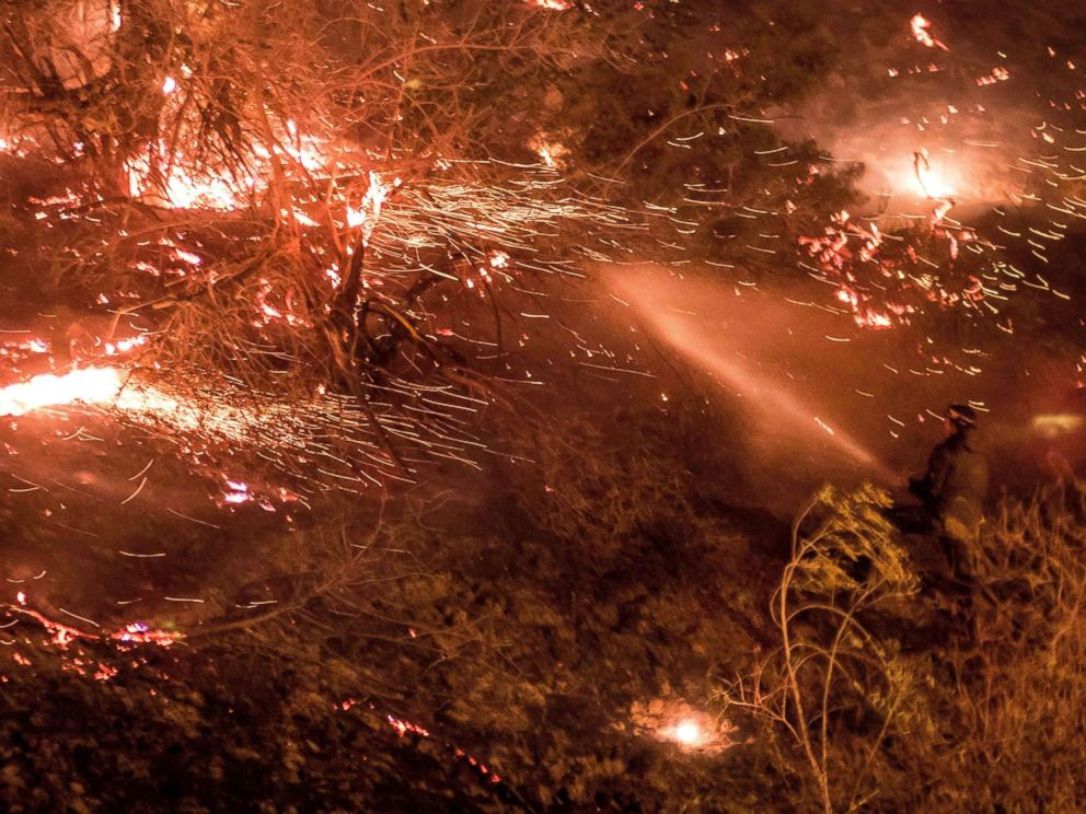 PHOTO: A man uses a hose to extinguish the Creek Fire as it burns along a hillside near homes and horses in the Shadow Hills neighborhood of Los Angeles, Calif., on Dec. 5, 2017.
