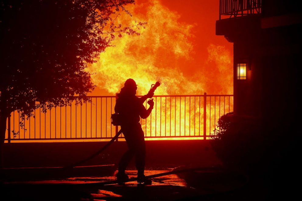 PHOTO: A firefighter waits for water as the Saddleridge fire flares up near homes in Sylmar, Calif., Oct. 10, 2019.