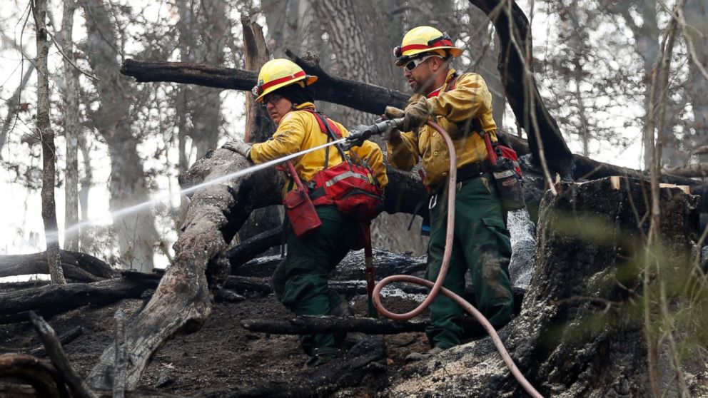 Firefighters Valarie Lopez, left, and Mark Tabaez work to cool hot spots after a wildfire burned a hillside, Nov. 15, 2016, in Clayton, Georgia.