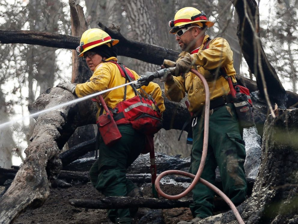 PHOTO: Firefighters Valarie Lopez, left, and Mark Tabaez work to cool hot spots after a wildfire burned a hillside, Nov. 15, 2016, in Clayton, Georgia.