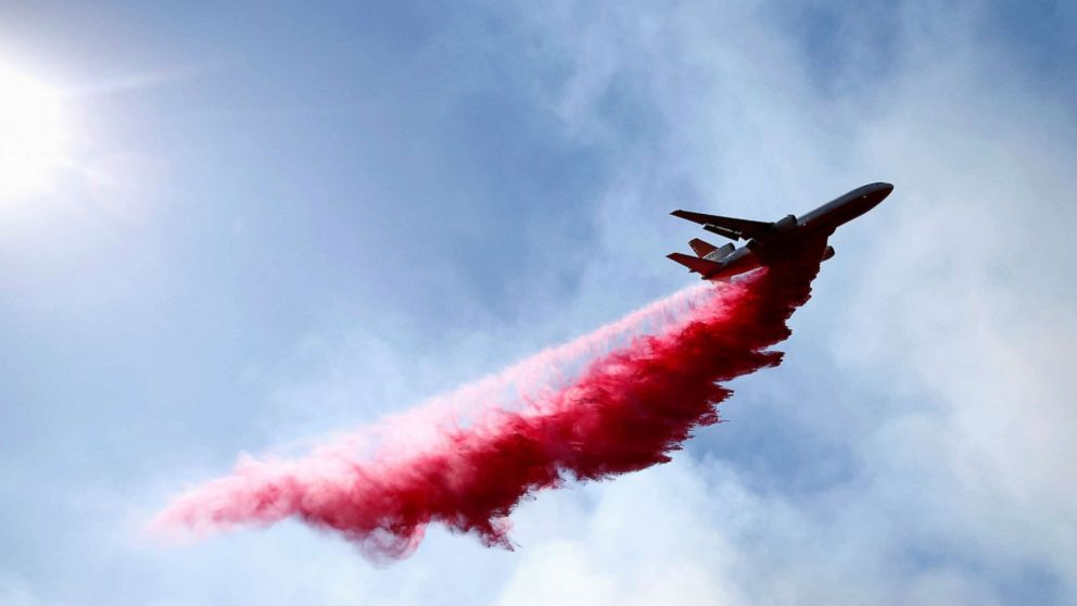 An aircraft drops flame retardant as firefighters battle the Woolsey Fire as it continues to burn in Malibu, Calif., Nov. 11, 2018.