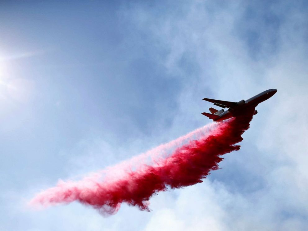 PHOTO: An aircraft drops flame retardant as firefighters battle the Woolsey Fire as it continues to burn in Malibu, Calif., Nov. 11, 2018.