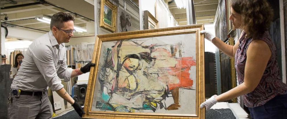 PHOTO: The recovered painting by Willem de Kooning is readied for examination by UA Museum of Art staff Nathan Saxton, left, and Kristen Schmidt.