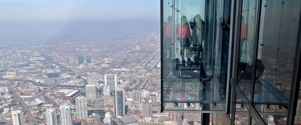 PHOTO: Visitors stand on the glass balcony at the skydeck of the Willis Tower in Chicago, Feb. 13, 2013.