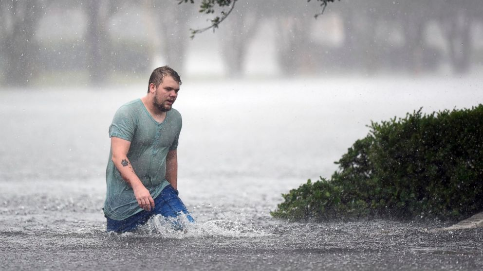Jake Head walks through heavy rain from tropical storm Florence in Wilmington, N.C., Saturday, Sept. 15, 2018.