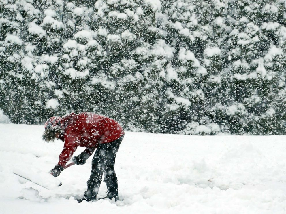 PHOTO: A woman shovels snow during a winter storm, March 7, 2018, in Springfield, Pa.