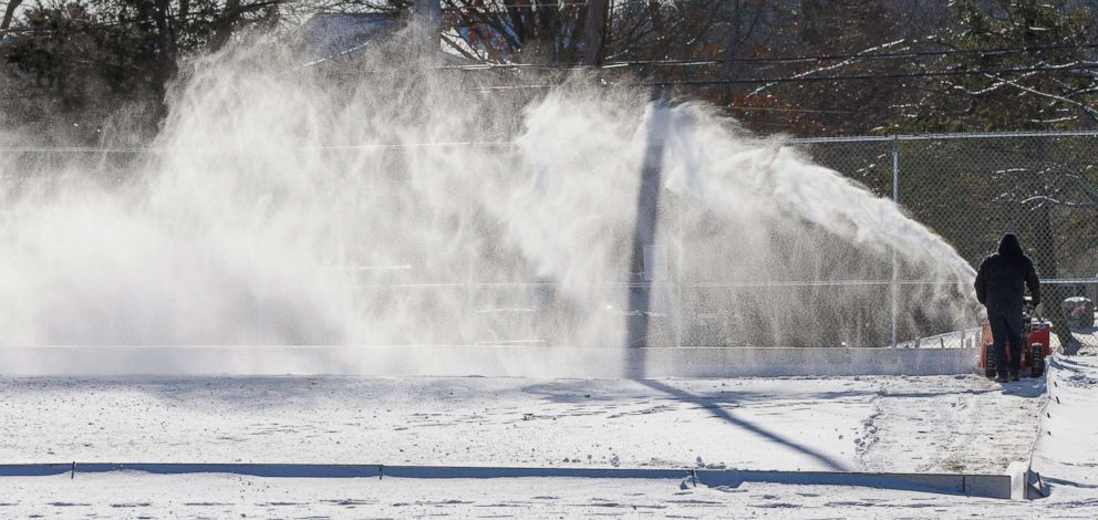 PHOTO: A town recreational employee clears snow from an outdoor skating rink in Burlington, Mass., Jan. 02 2018.