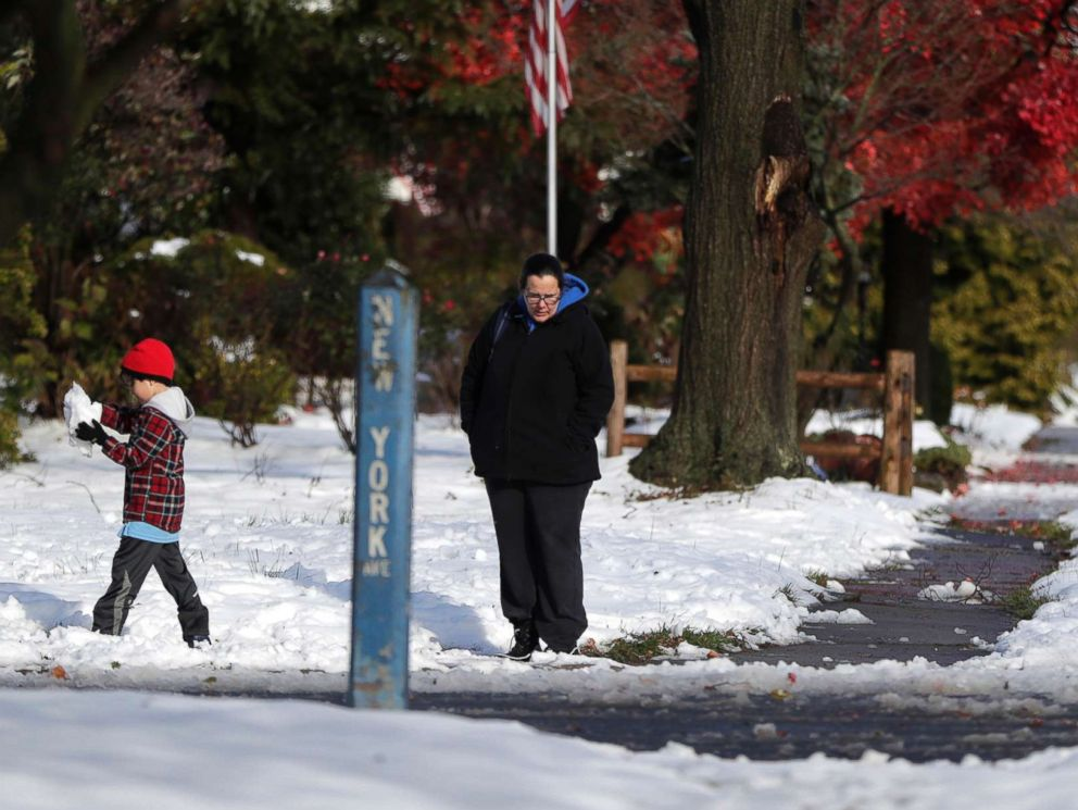 PHOTO: A woman waits with a child for a school bus the morning following a snowstorm, Friday, Nov. 16, 2018, in Metuchen, N.J.
