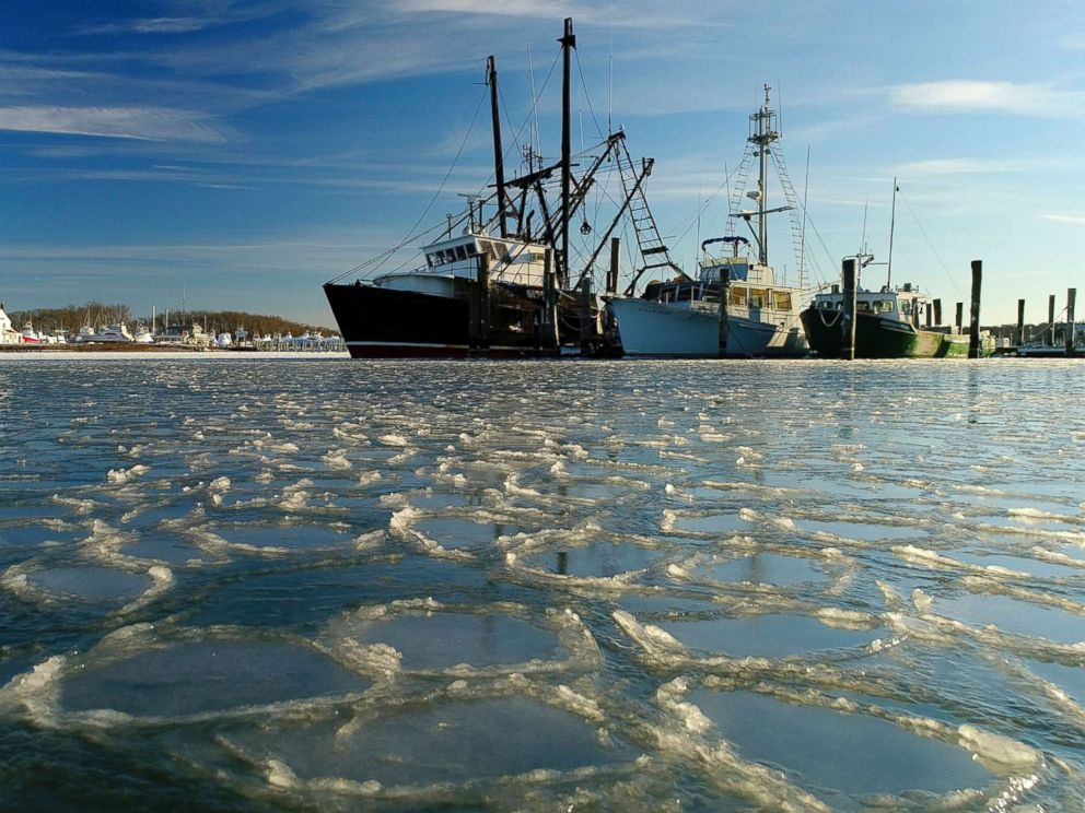 PHOTO: Fishing trawlers sit on the frozen harbor of Lake Montauk surrounded by thin sheets of ice, Jan. 7, 2018, in Montauk, N.Y.