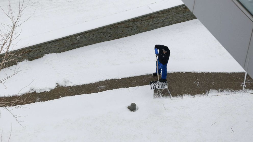 A Massport employee clears snow on a walk way at Boston Logan International Airport, Jan. 30, 2018, in Boston. A late January snowstorm left two inches in the greater Boston area and caused several delays at the airport.