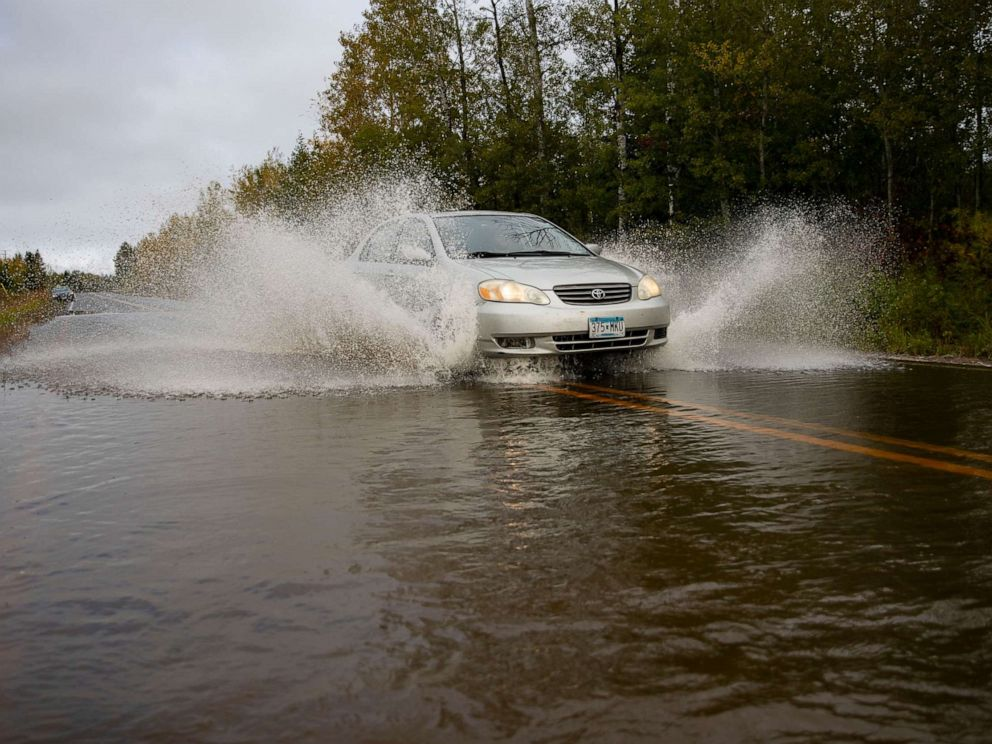 PHOTO: A car passes through high water in a section of County Highway K in South Range, Wis, Monday, Sept. 30, 2019. The road was washed out and eventually closed off on Monday morning due to heavy rain that started Sunday night.