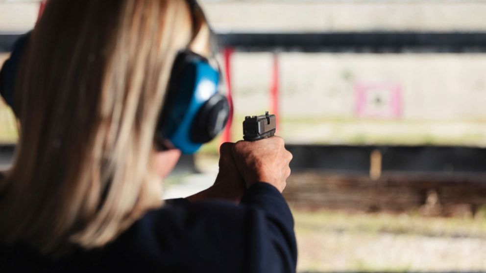 A woman at the shooting range aiming a gun in an undated stock photo.