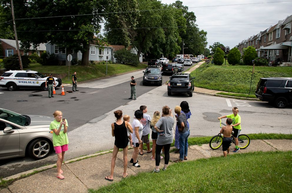 PHOTO: Community members gather as rescue personal remove the bodies of two workers who were found dead in a sewer manhole in Alden, Pa., July 11, 2019.