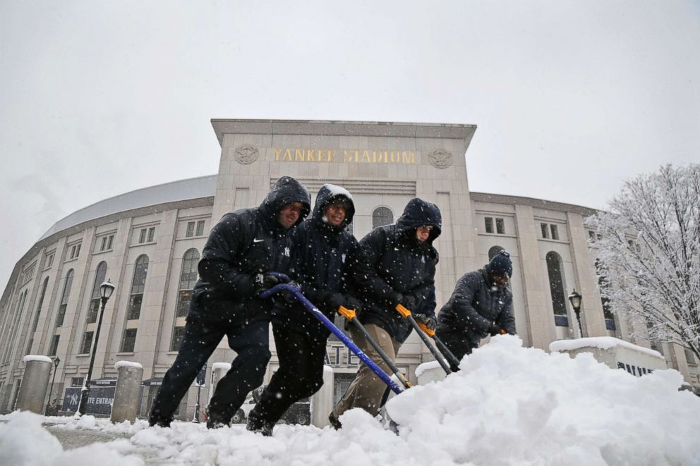 PHOTO: Men shovel snow from the sidewalks in front of Yankee Stadium before the New York Yankees home opener against the Tampa Bay Rays, April 2, 2018, in New York.