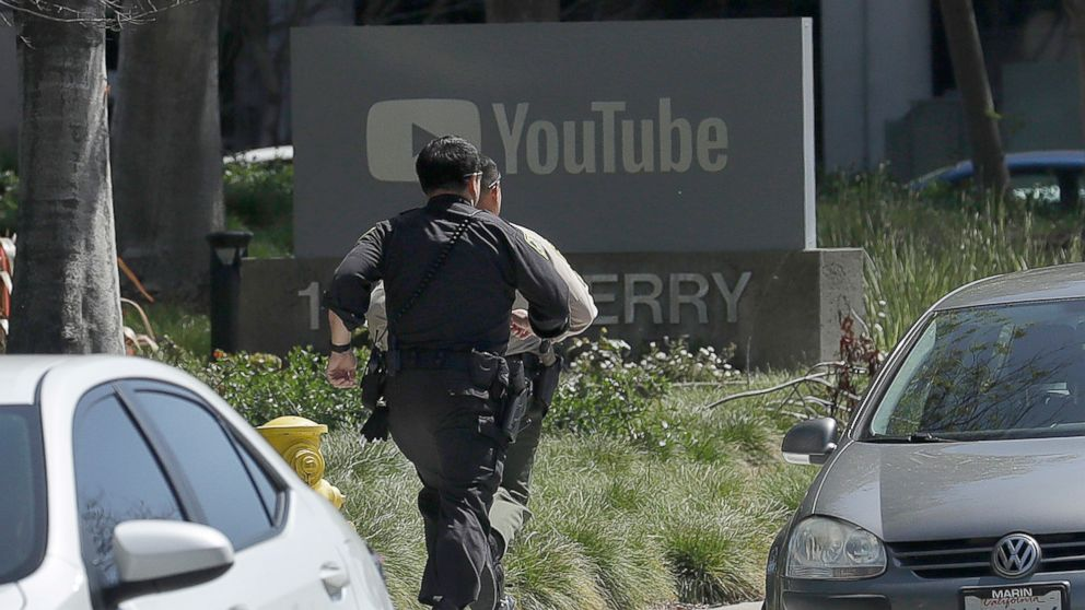 Officers run toward the YouTube offices in San Bruno, Calif., April 3, 2018.